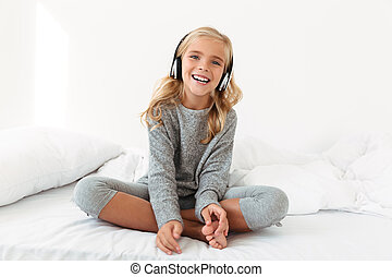 Happy little girl in gray pajamas listening to music while sitting in her bed