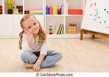 Happy little girl in her room sitting