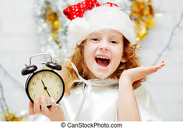 Happy little girl in Santa hat holding a clock in his hands. Chr