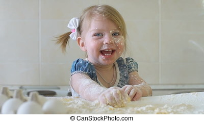 Happy little girl in the kitchen playing with flour, slow motion.