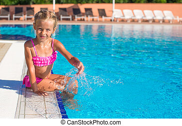 Happy little girl in the swimming pool looking at camera
