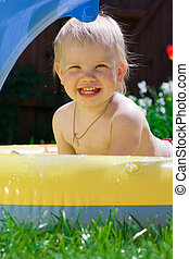 Happy little girl in yellow pool