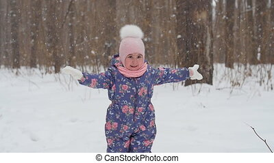 Little girl is playing with snow in the park