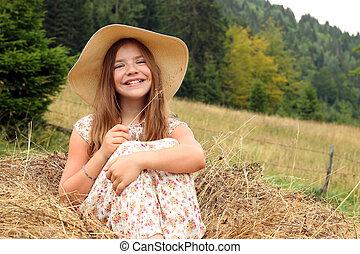happy little girl is sitting in the hay portrait