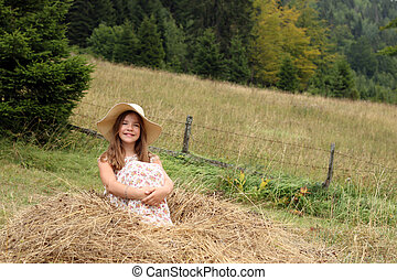 Happy little girl is sitting in the hay