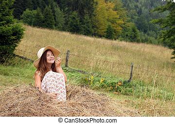 happy little girl is sitting in the hay summer season