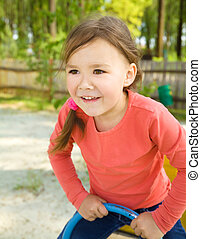 Happy little girl is swinging on see-saw - Cute and happy...
