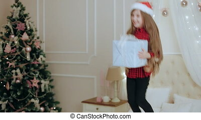 Happy little girl jumping on bed with gift box