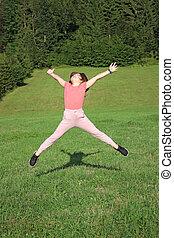 happy little girl jumping on field