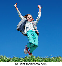 Happy little girl jumping on meadow