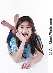 Happy little girl lying on floor