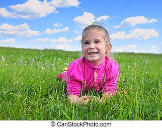 happy little girl lying on grass