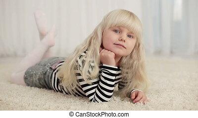 Happy little girl lying on the carp