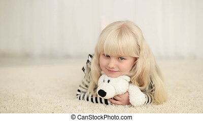 Happy little girl lying with teddy