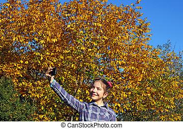 happy little girl makes selfie in the park autumn season