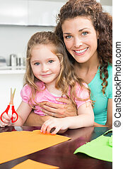 Happy little girl making paper shapes with mother at the table