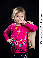 Happy little girl, model with a jacket on the shoulder. Black background, studio photo.
