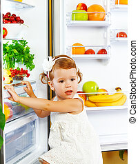happy little girl near the fridge with healthy foods, fruits and vegetables