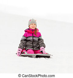 happy little girl on sled outdoors in winter