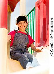 happy little girl on slide at children playground
