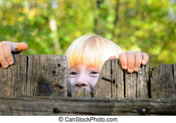 Happy Little Girl Peeking on Wooden Fence