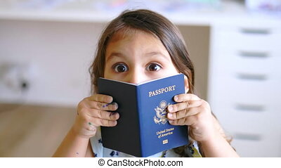 Happy little girl opening her eyes wide open and playfully hiding behind American passport. Joyful young girl playing with American passport. Children having fun at home