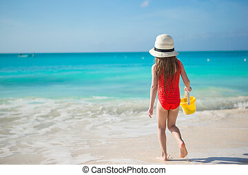 Happy little girl playing at beach during caribbean vacation
