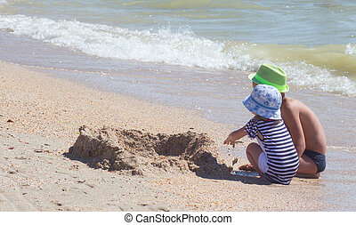 Happy little girl playing at beach during summer vacation