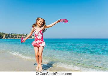 Happy little girl playing in the sea