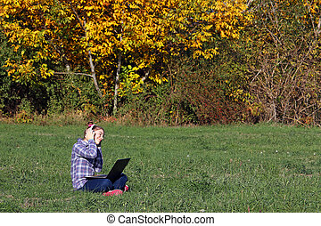 Happy little girl playing laptop and listening music on headphones in the park