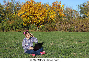 happy little girl playing laptop and talks on smartphone