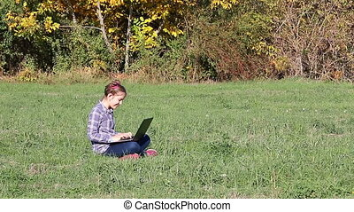 happy little girl playing laptop in the park autumn season