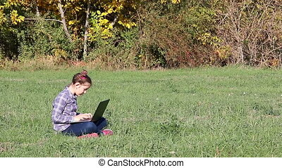 happy little girl playing laptop in the park