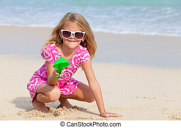 Happy little girl  playing on the beach