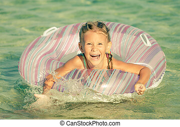 Happy little girl playing on the sea