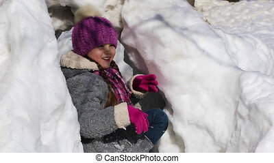 Happy little girl playing snowballs