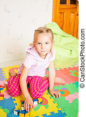 Happy little girl playing with blocks