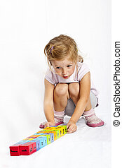 happy little girl playing with colourful wooden blocks