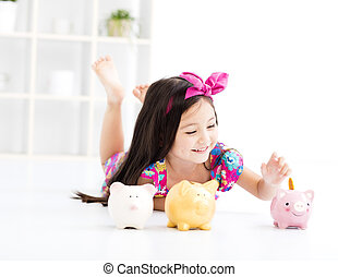 happy little girl playing with piggy bank