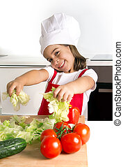 happy little girl playing with vegetables at home kitchen in apron and cook hat