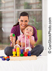 happy little girl playing wooden toy