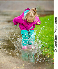 Happy little girl plays in a puddle - Happy little girl...