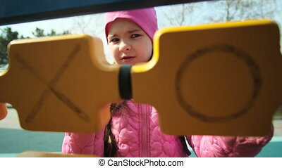 Happy little girl plays in the playground in cool weather. ...