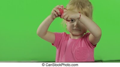 Happy little girl plays with plasticine on chroma key...