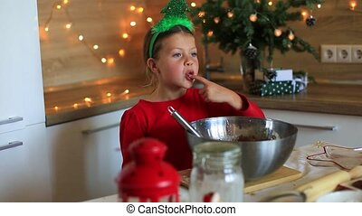 Happy little girl prepares cookies on the eve of christmas.