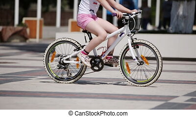 Happy little girl riding a bicycle in the city park at summer sunshine day.