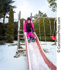 little girl riding down the slide on playground at snowy day