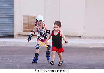 Happy little girl roller skates on asphalt and boy with boomerang runs in summer evening