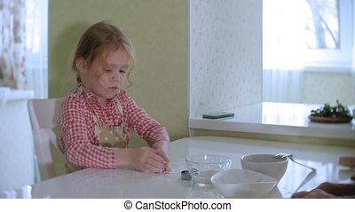 Happy little girl rolling biscuit dough at home in the kitchen