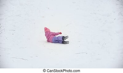 Happy little girl rolling in snow and having fun
